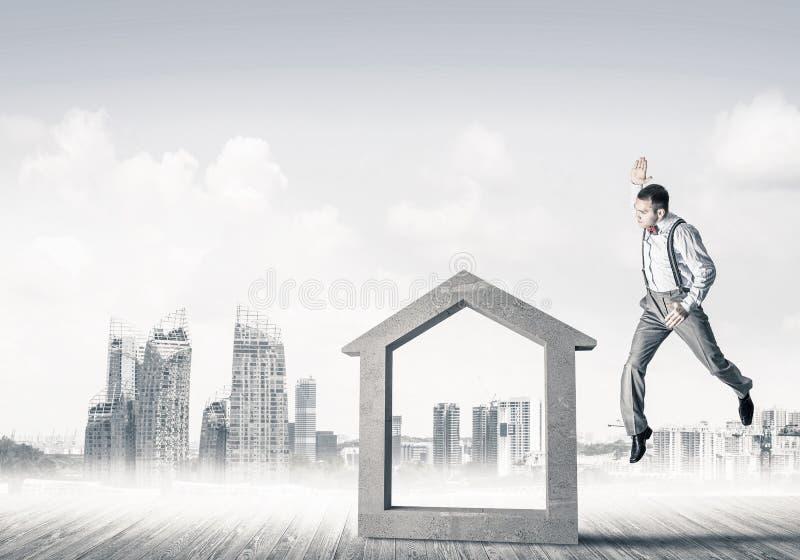 Managermannzusammenstoßendes Steinhaus als Symbol für Immobilien insura stockfoto
