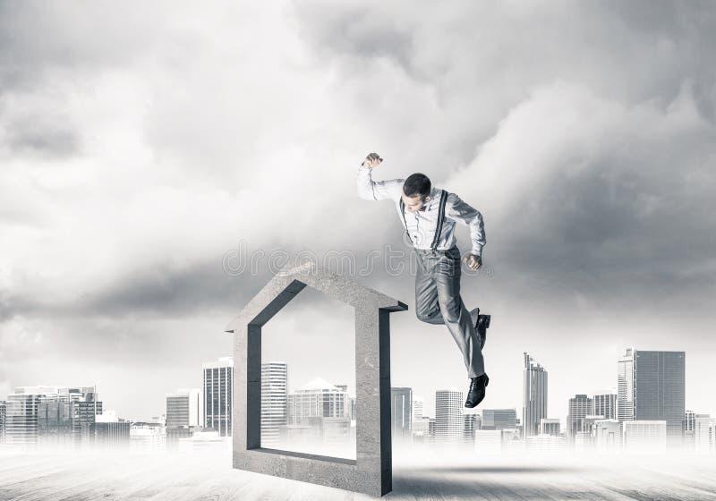 Managermannzusammenstoßendes Steinhaus als Symbol für Immobilien insura lizenzfreie stockfotos