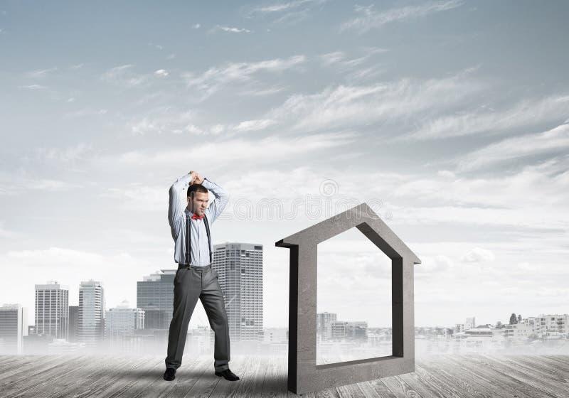 Managermannzusammensto?endes Steinhaus als Symbol f?r Immobilienversicherung stockfoto