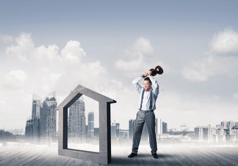 Managermannzusammensto?endes Steinhaus als Symbol f?r Immobilienversicherung lizenzfreie stockfotos
