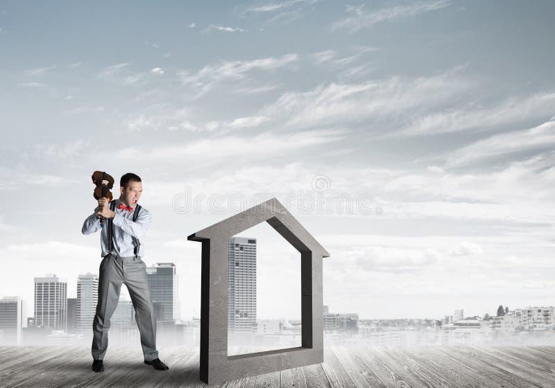 Managermannzusammensto?endes Steinhaus als Symbol f?r Immobilienversicherung stockbild