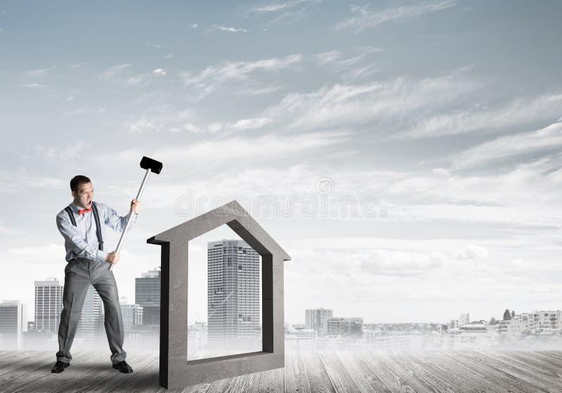 Managermannzusammensto?endes Steinhaus als Symbol f?r Immobilienversicherung stockfotografie