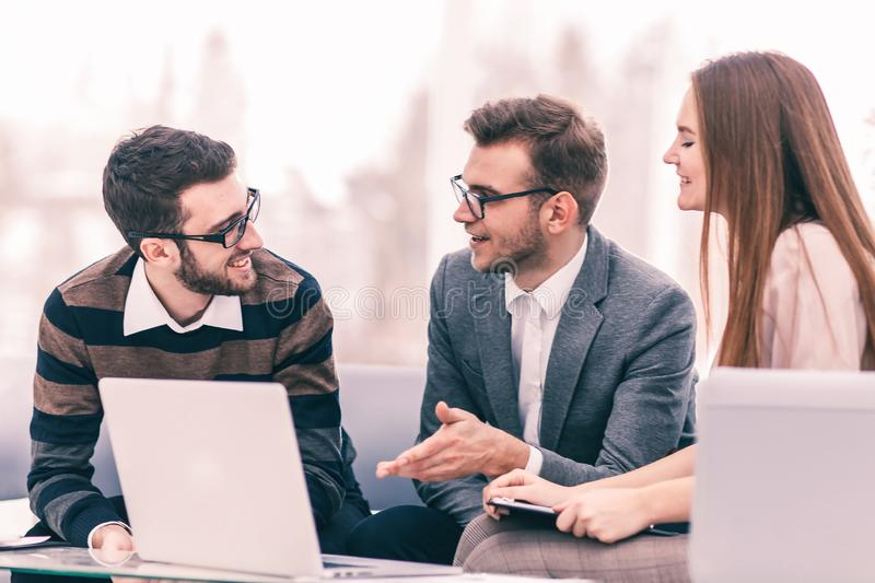 Managers of the company and the client, discussing the terms of the new contract and look at the laptop screen with the stock photography