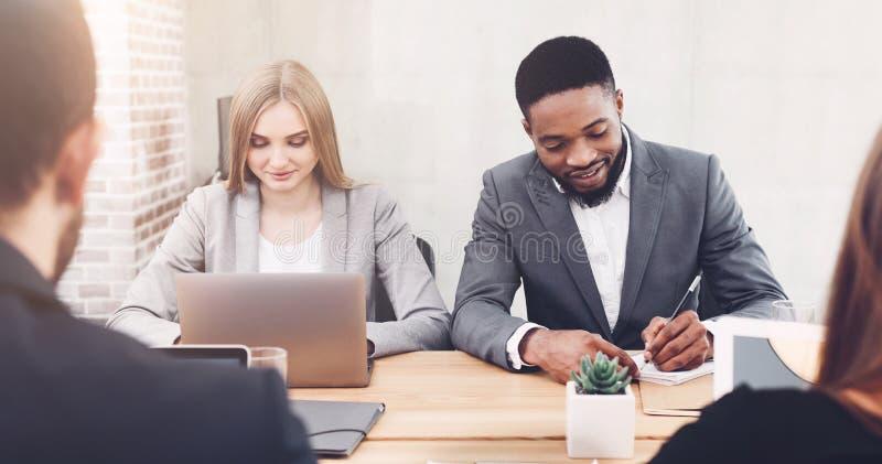 Managers die in bureau werken, laptop met behulp van en ideeën schrijven stock foto