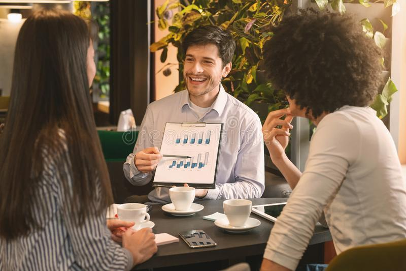 Managers die grafiek analyseren bij een bedrijfslunch stock afbeelding
