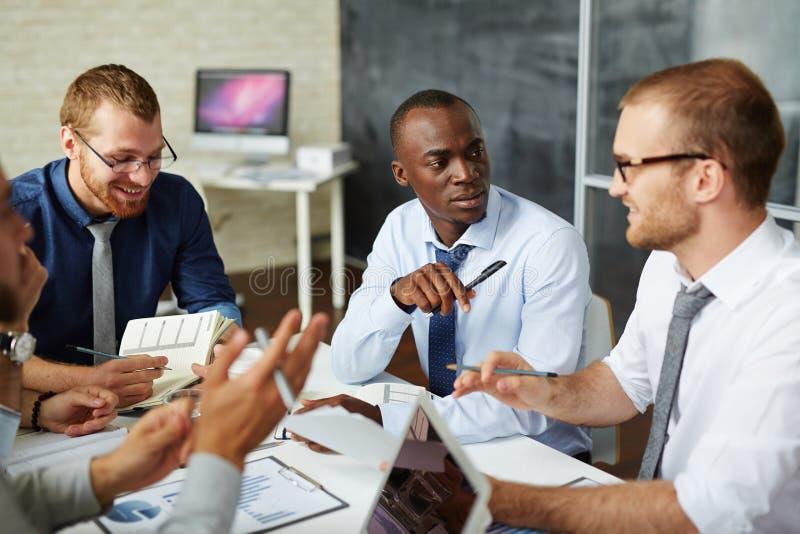 Managers die ideeën bespreken stock foto's