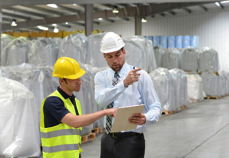 managers and workers in the logistics industry talk about working with chemicals in the warehouse royalty free stock image