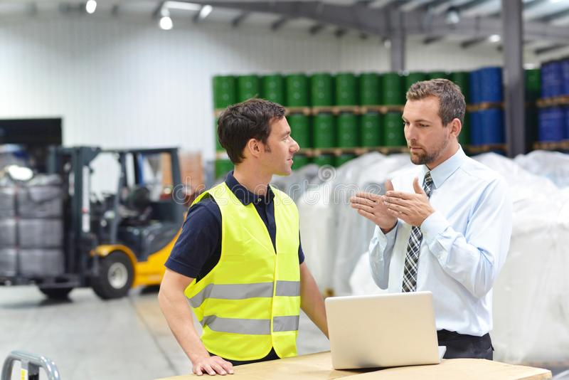 managers and workers in the logistics industry talk about working with chemicals in the warehouse royalty free stock photography