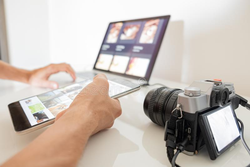 Managing digital images on a computer. Human hands hold a tablet to organize or import images from camera to laptop stock photos