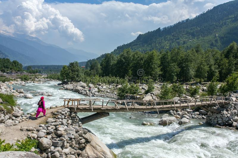 Unidentified indian woman walk on the wooden bridge near Vashisht village in Kullu valley, Himachal Pradesh, India. Manali, India - May 27, 2017: Unidentified royalty free stock images