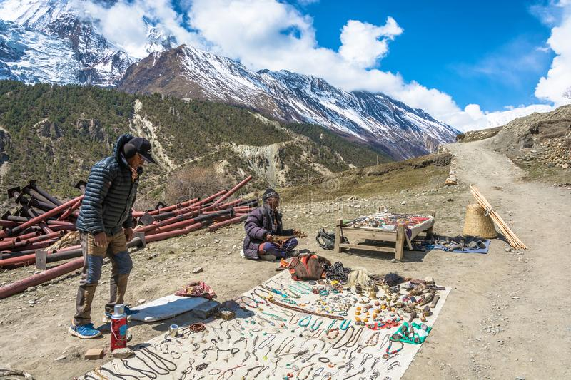 Two Nepalese sell local Souvenirs on April 5, 2018 in the mountain village of Manang in the Himalayas , Nepal. royalty free stock photography