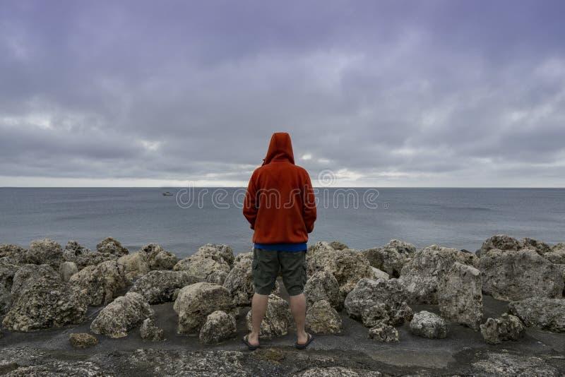 Mananseende bredvid havet som ser över en skyddsmur mot havet fotografering för bildbyråer