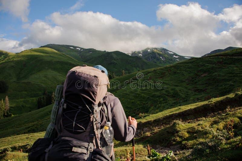 Mananseende för bakre sikt på kullen med att fotvandra ryggsäcken och pinnar som ser landskapet royaltyfria bilder