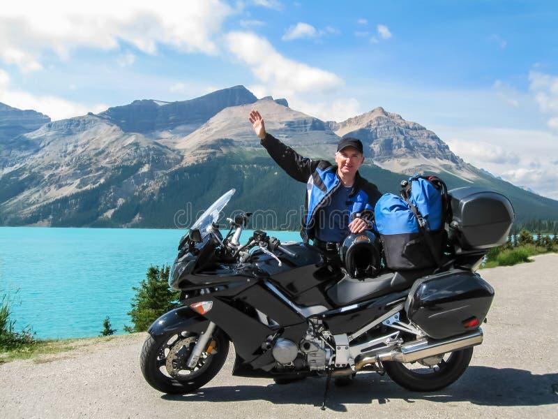 Mananseende, genom att vinka för motorcykel fotografering för bildbyråer