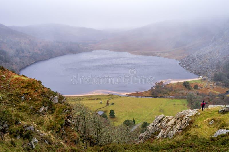 Mananseende på kanten av klippan på vattenbehållaren som in ser till avlägsen mist som täcker sjö- och bergframtid som tänker om  royaltyfri fotografi