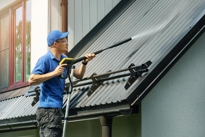 Mananseende på stege och rengörande husmetalltak med högtryckpackningen arkivbilder