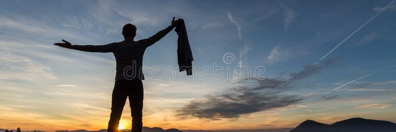 Mananseendet under glödande röd aftonhimmel med hans armar fördelade brett royaltyfri foto