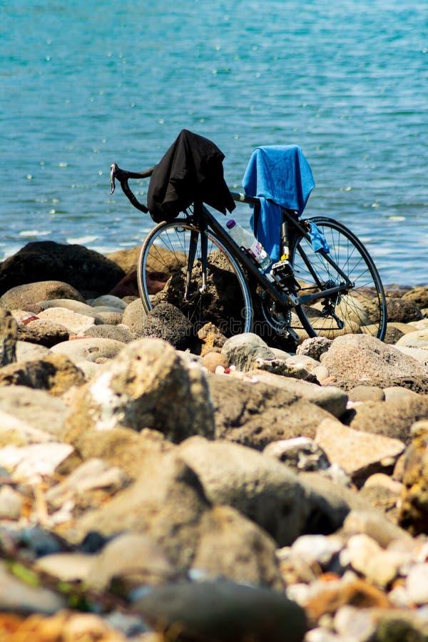 Manapany, Франция - 27-ое сентября 2018: Велосипед припаркованный на каменистом пляже пока владелец принимает заплыв стоковое изображение rf