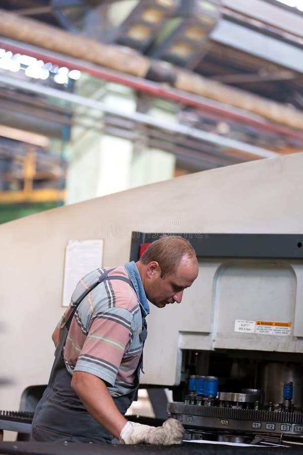 Manarbetare på fabriksseminariet som justerar utrustning royaltyfria bilder
