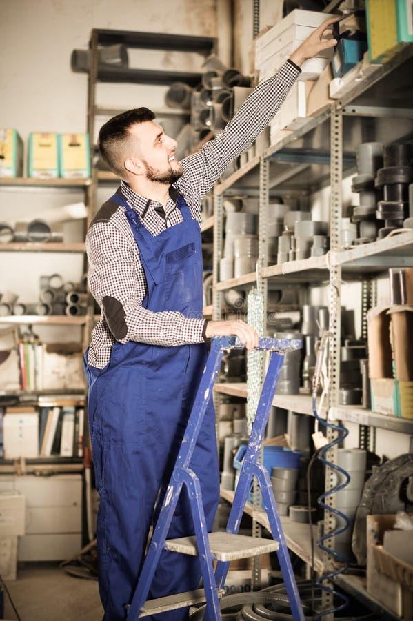 Manarbetare som går till och med detaljer för sanitär teknik i worksho arkivfoto