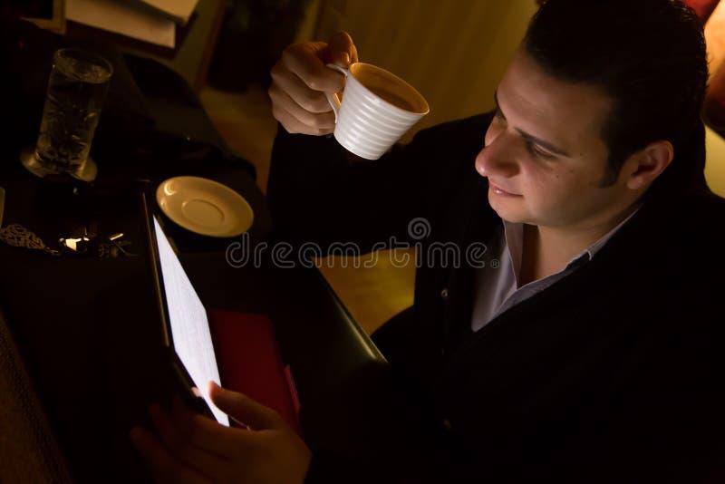 Manarbete på minnestavlaPC och den hållande kaffekoppen royaltyfria foton