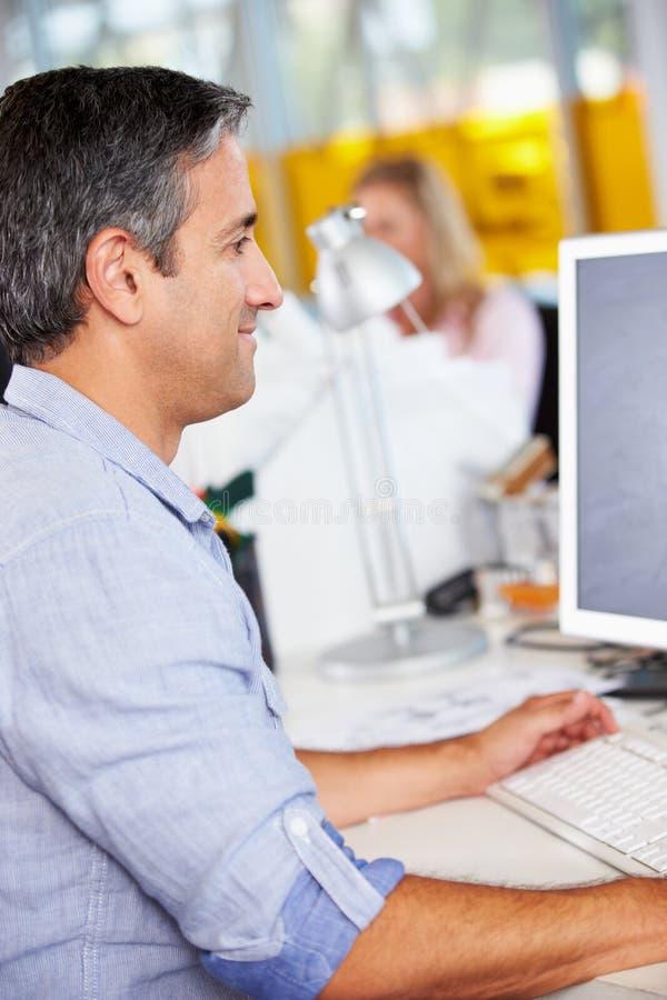Manarbete på skrivbordet i upptaget idérikt kontor arkivfoton