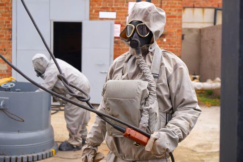 Manarbeten i en vit kemisk skyddsdräkt och en gasmask arkivfoton