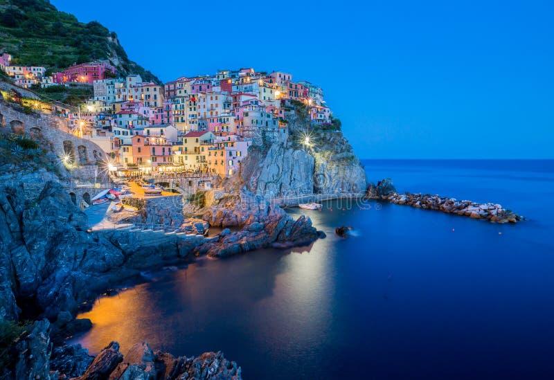 Manarola, Cinque Terre no crepúsculo com as luzes que cintilam imagens de stock royalty free