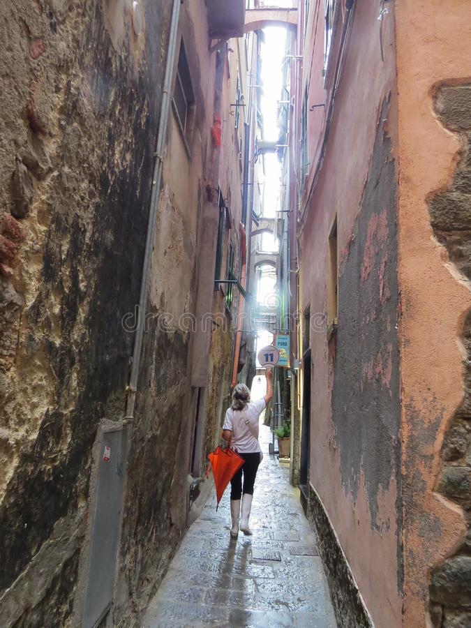 On a rainy summer day, the guide conducts a tour of the narrow street of the coastal city of Manarola royalty free stock images