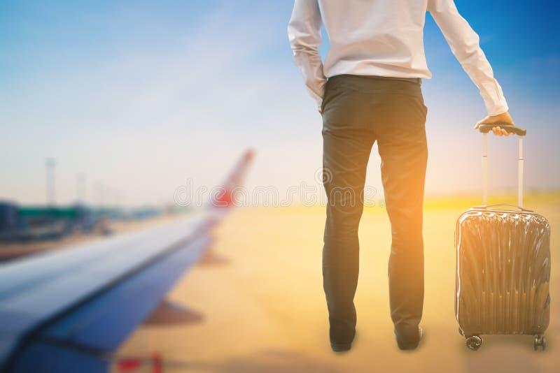 Manasiat som rymmer bagage och står på flygplanbakgrund för frihet för aktivitetslivsstildet fria eller loppturism och welco royaltyfri fotografi