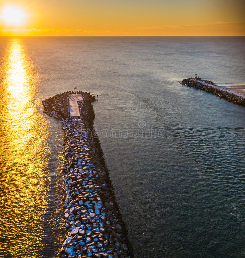 Manasquan inlet at sunset. A golden sunset over the Manasquan Inlet in New Jersey, United States which connects the Atlantic Ocean with the Manasquan River stock photo