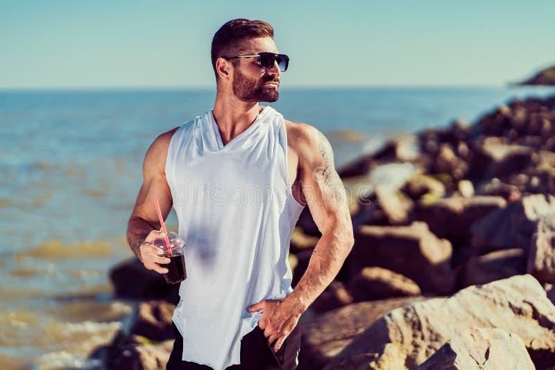 Manat tatuado barbudo el centro turístico en una camisa blanca y las gafas de sol, sentándose en una roca, cóctel de la bebida en imagenes de archivo