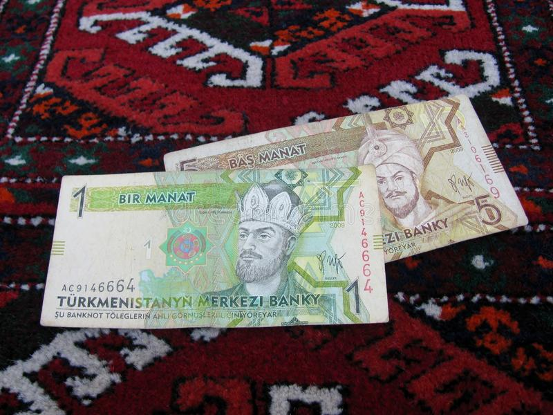 1 and 5 manats banknotes a Turkmen rug stock image