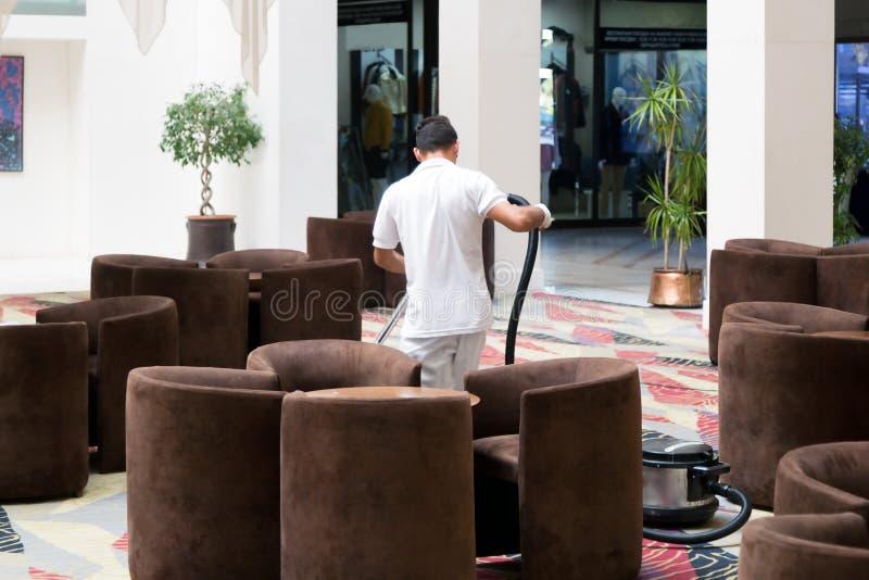 Manavgat, Turkije, het Hotelarbeider van 09/07/2019 met een stofzuiger redactie stock afbeelding