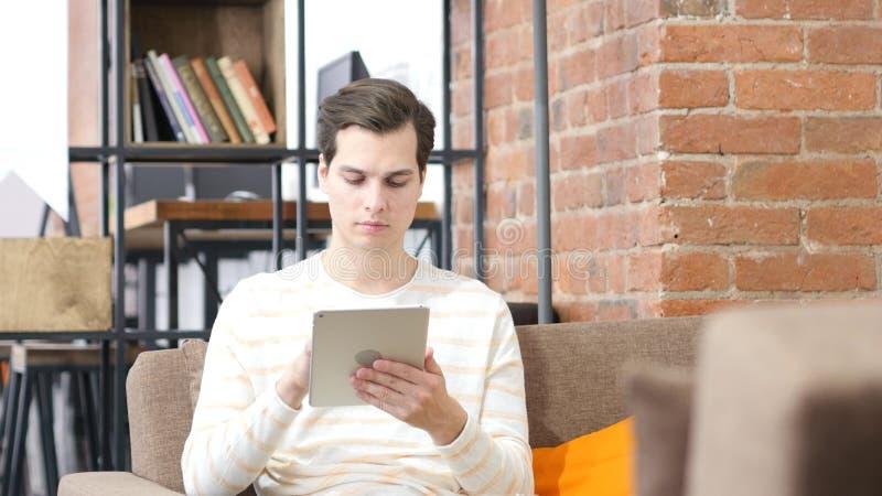 Manbankiren söker information i finansmarknad via den digitala minnestavlan royaltyfri foto