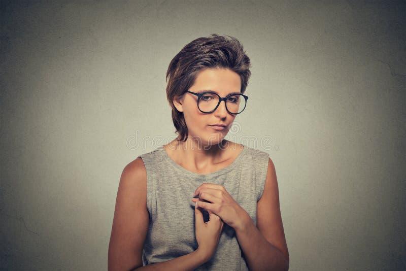 Mancanza di fiducia La giovane donna timida in vetri ritiene maldestra immagini stock libere da diritti