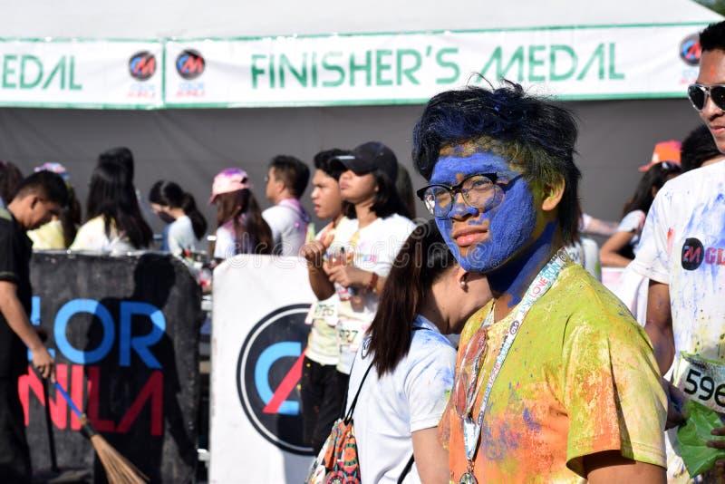 Manchado com as tinturas coloridas, jovens que têm o divertimento na corrida do brilho de Manila da cor fotografia de stock