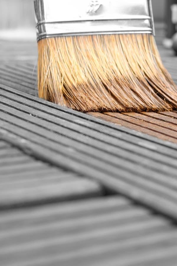 Manchando o decking de madeira em um jardim com um pincel fotografia de stock royalty free