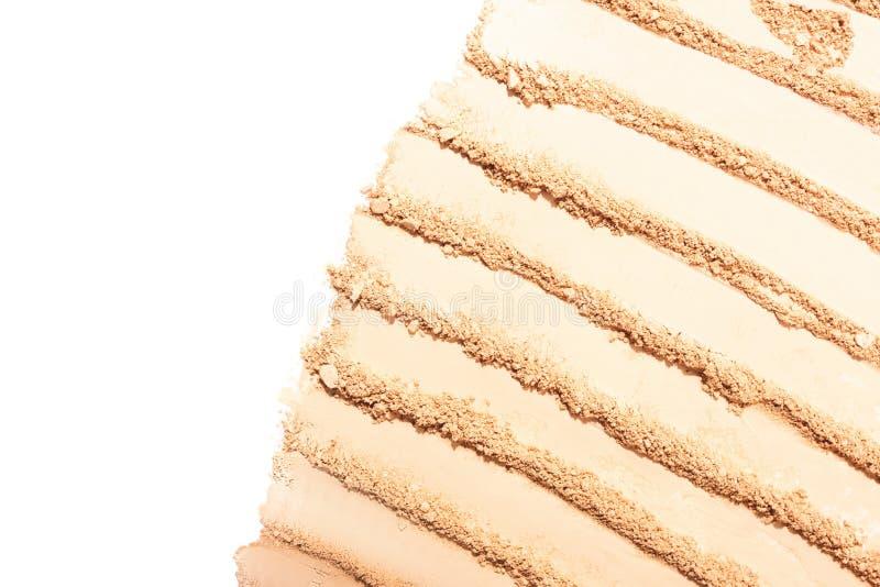 Manchas beige ligeras del polvo de cara en el fondo blanco imagenes de archivo