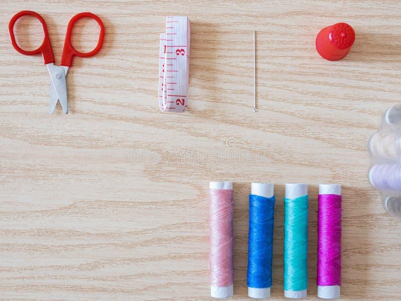Manchas de fios, bobina, tesoura e acessórios de costura sobre fundo de madeira imagem de stock