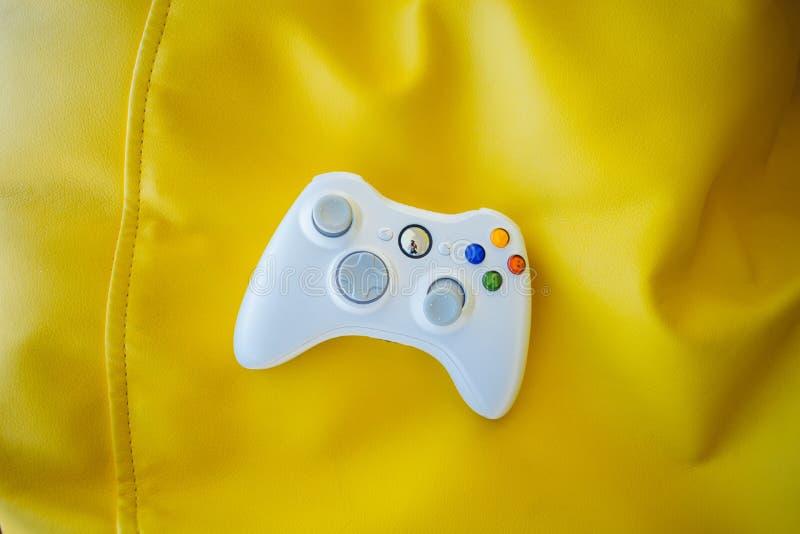 Manche branco para o console do jogo em um fundo amarelo brilhante Gamepad em um fundo de cadeiras amarelas do saco fotografia de stock royalty free
