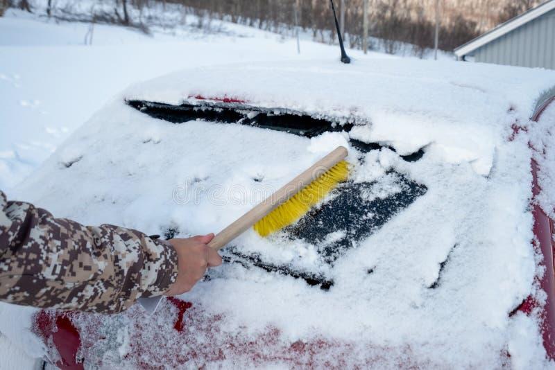 Manche utilisant la neige de balayage de brosse sur la voiture de pare-brise photographie stock libre de droits