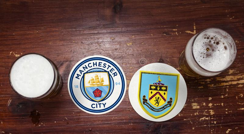 Manchester City vs. Burnley. Football team logos on beer mat at the pub with pints of beer royalty free stock photo