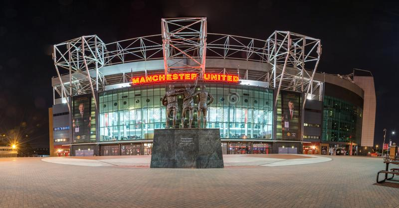 MANCHESTER, ENGLAND - September 29, 2017: Panorama of the stadium Old Trafford and the statue 'United Trinity' in the night royalty free stock images