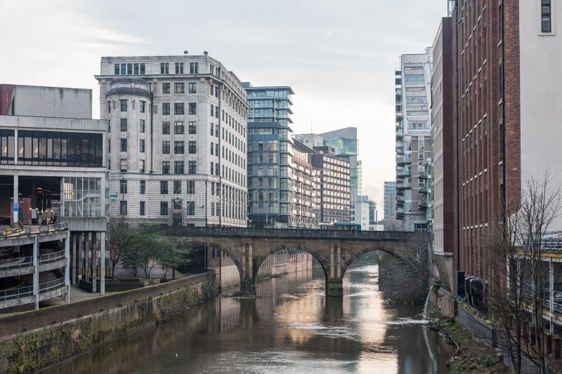 MANCHESTER, INGLATERRA - 8 DE MARZO DE 2014: Paisaje urbano de Manchester con el río y los edificios foto de archivo