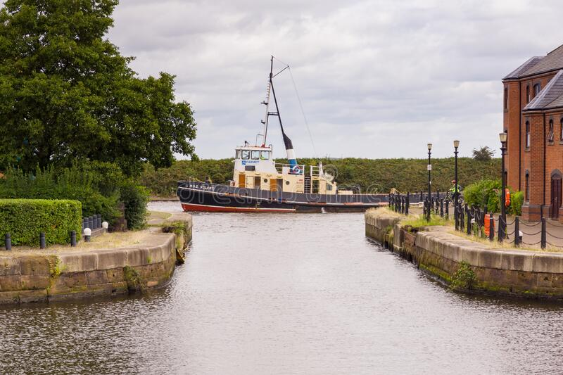 Manchester Ship Canal. The tug boat M. S. C. Volant navigating the Manchester ship canal passing the old docks at Ellesmere Port stock photography