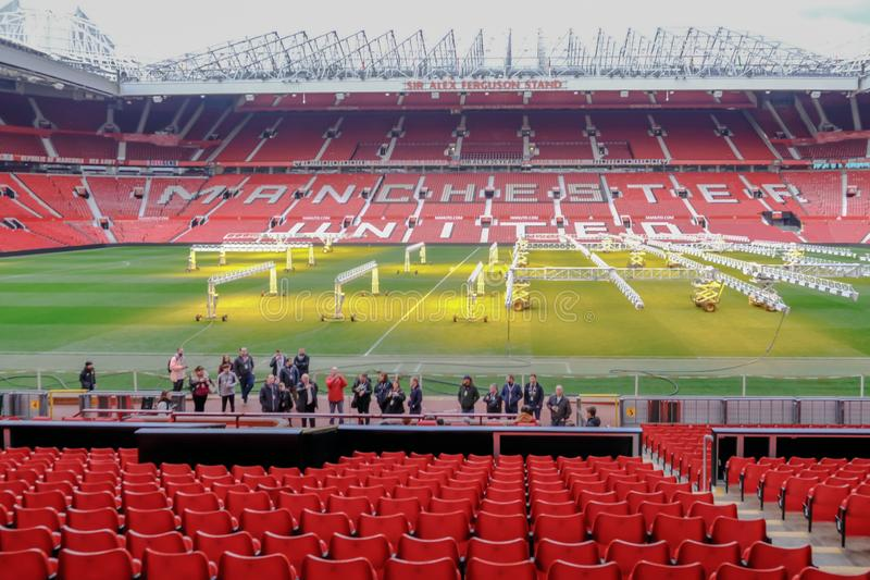 Manchester United`s Old Trafford stadium.  Seating is empty and the pitch is having light treatment to help maintain the grass royalty free stock photo