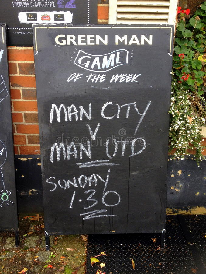 Manchester United versus Manchester City. Bracknell, United Kingdom - October 31, 2014: Blackboard sign outside The Green Man Public House advertising TV royalty free stock photography