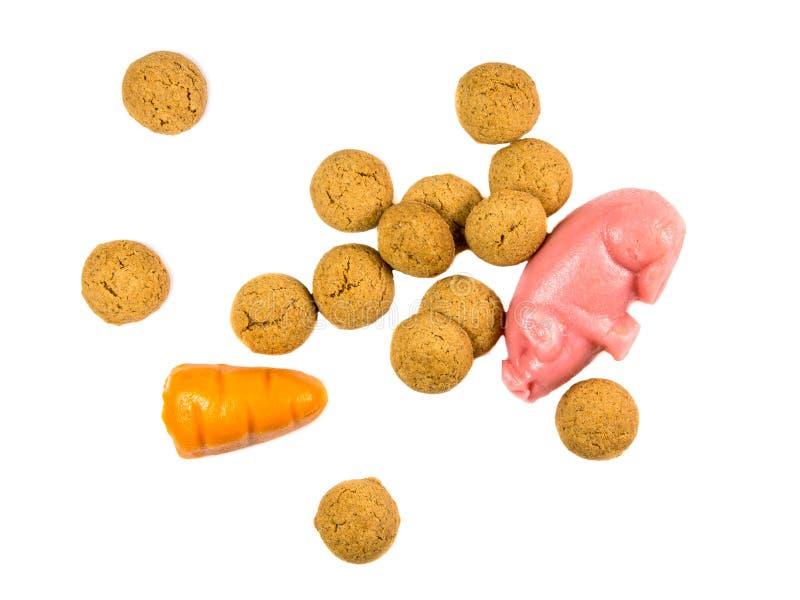 Manciata di biscotti di Pepernoten con il maiale e la carota del marzapane fotografia stock