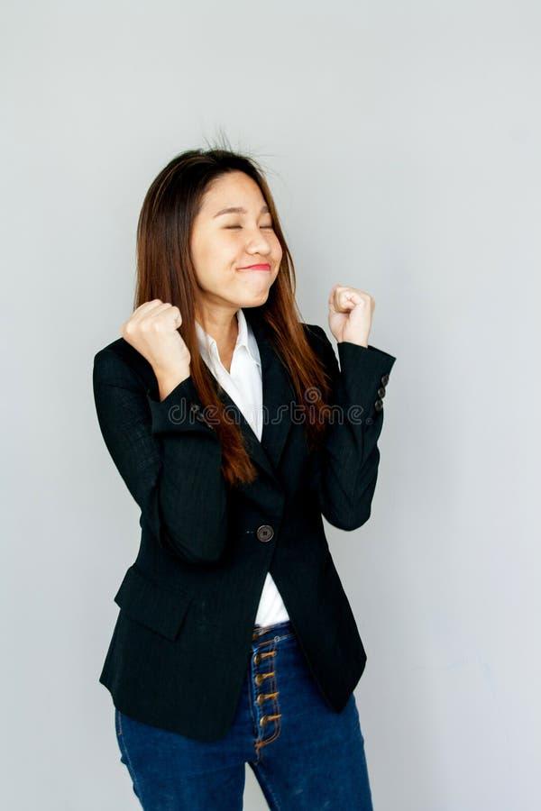 Manciata e sorriso asiatici di manifestazione di signora del ritratto sull'isolato grigio immagini stock libere da diritti